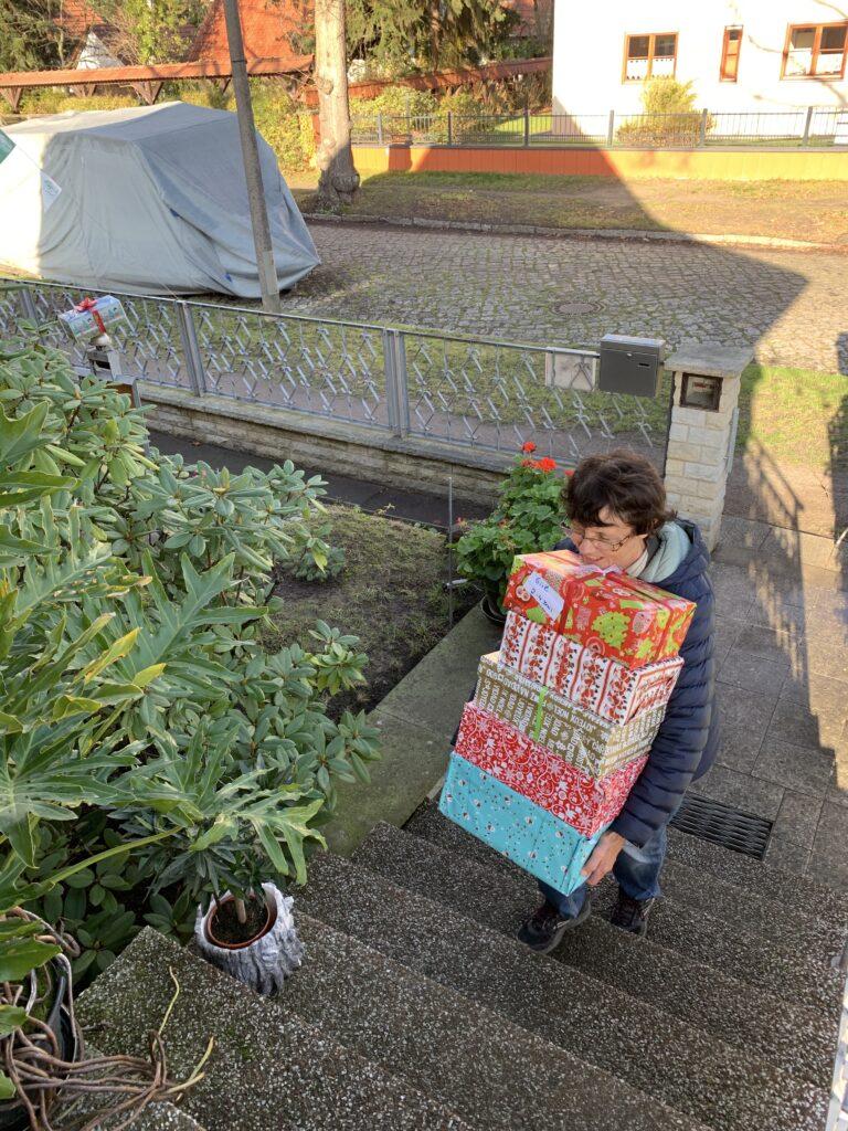 Eine Helferin trägt die Mahlsdorfer Geschenkkartons in die Sammelstelle. Foto: Mile Impe